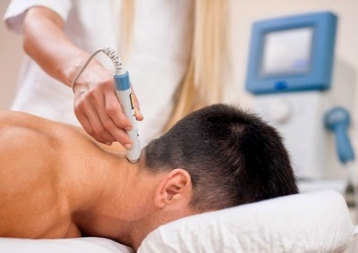 Therapeutic laser technology - therapist pointing medical laser beam to a spot on a patient's neck